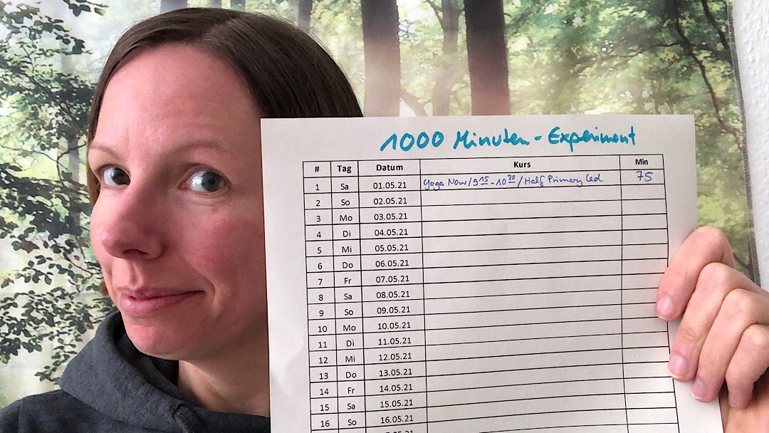 Marie mit einer Liste in der Hand mit den Tagen des Monats und der Überschrift 1000 Minuten Experiment. In der ersten Zeile ist etwas eingetragen.