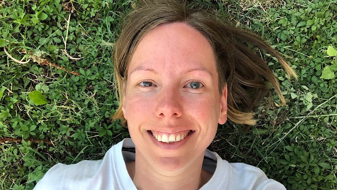 Frau auf dem Rücken im Gras liegend