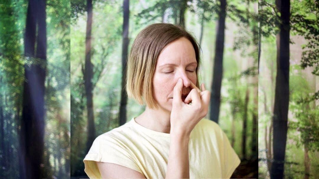 Frau hält sich mit zwei Fingern in einem Yogamudra ein Nasenloch zu
